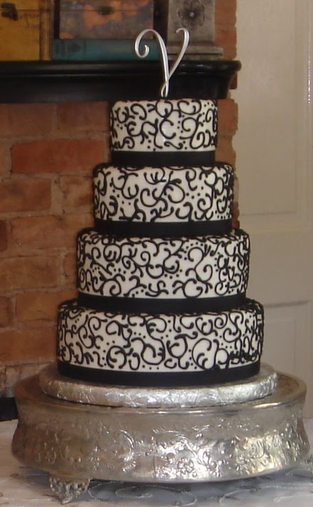Four tier white fondant wedding cake with black scrolls and ribbons
