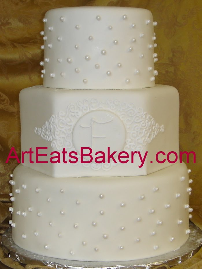 white fondant wedding cake with sugar pearls monogram and curlicues